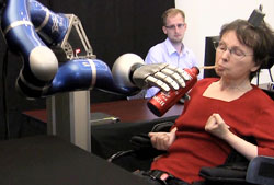 A BrainGate microelectrode was implanted in the motor cortex of a 58-year-old woman, paralyzed by a stroke for almost 15 years. She uses her thoughts to control a robotic arm, grasp a bottle of coffee, serve herself a drink, and return the bottle to the table. (Credit: Brown University)
