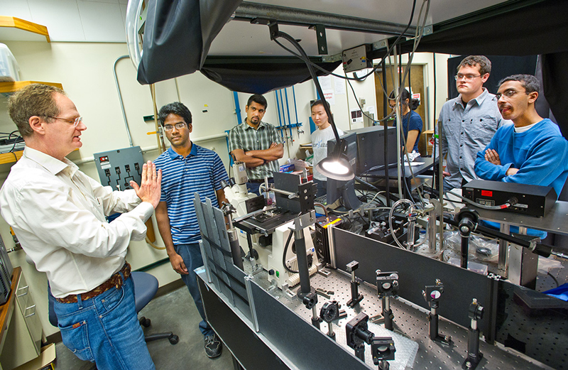 Kavli ENSI director Paul Alivisatos with his students at a laser lab. (Credit: Lawrence Berkeley National Lab - Roy Kaltschmidt, photographer)
